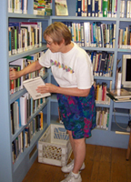 Volunteer putting books on the shelf